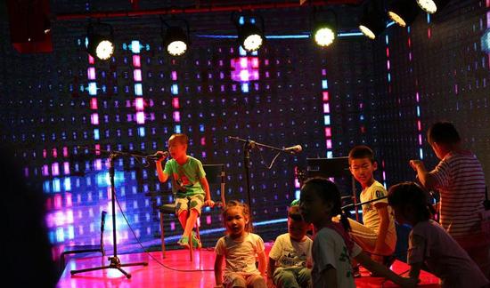 """舞台表演空档,在大唐不夜城游玩的孩子们""""抢占""""舞台,开始表演。"""