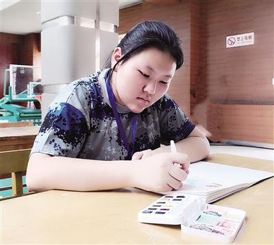 陕师大新生蒋山在精心绘制军训生活照 本报记者 张彦刚摄