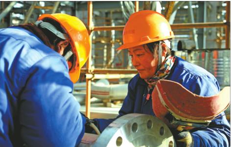 延安煤?#25512;?#36164;源综合利用项目施工人员在焊接管道。 本报通?#23545;?李晓军摄