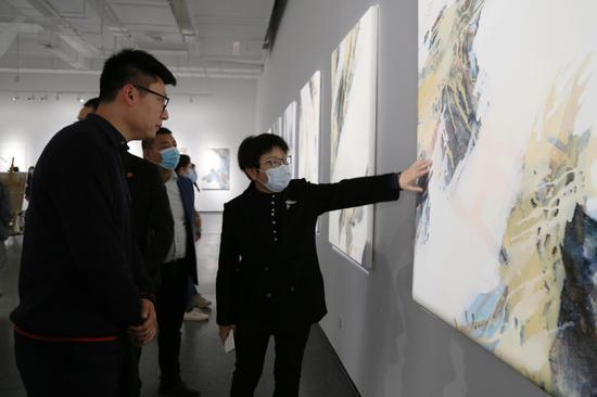 艺术家霍东泽为西安培华学院建筑与艺术设计学院常务副院长徐莹介绍作品