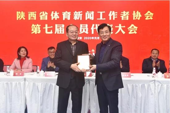 新当选的陕西体育新闻工作者协会主席高西广(右)为秘书长杨晓波颁发聘书