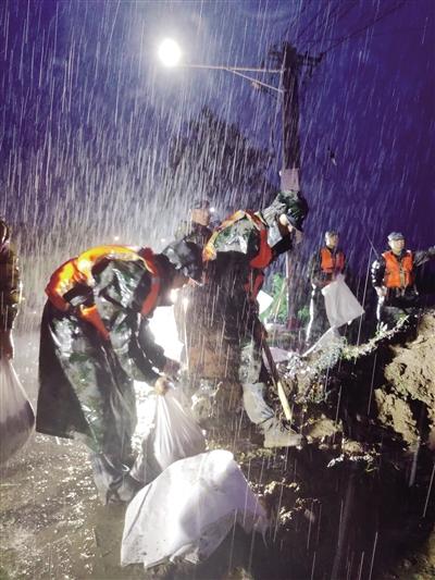 7月21日,驻扎在开封地区的空降兵某旅官兵冒雨在贾鲁河祥符区段加固堤坝。 新华社发