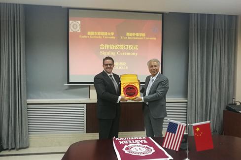 图:西安外事学院董事长黄藤(右)代表学校向东肯塔基大学校长Michael Benson(左)赠送礼物