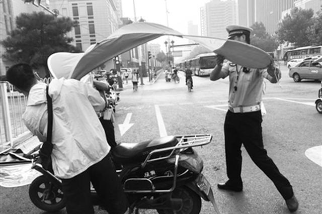 """西安街头电动车加装""""夺命伞""""现象普遍 一周查处919"""