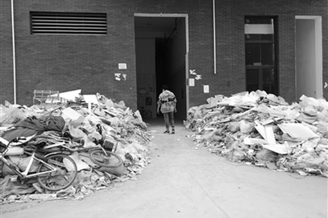 楼道门口建筑垃圾堆成山 西安一小区住户叫苦不迭