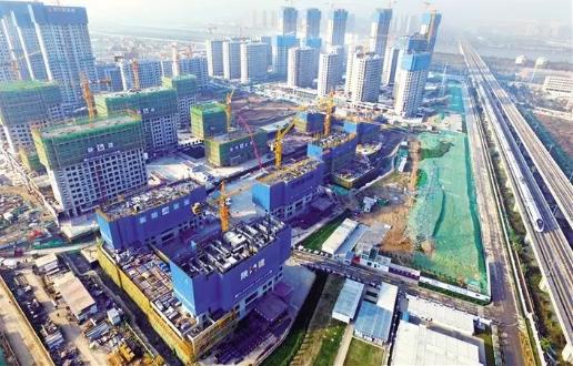11月19日,一列高速列车驶过正在建设中的西安全运村。西安全运村为2021年全运会的配套项目,其中十五栋楼将作为运动员的公寓在赛事期间使用。该村一至六地块(建筑)由陕建集团承建。陕西日报记者 袁景智摄