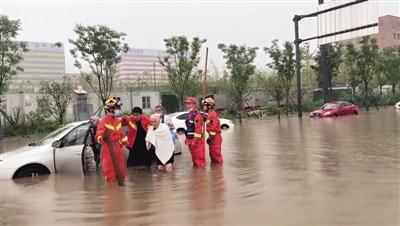 昨日,西安部分地区突降暴雨,一名80多岁的老太太被困车内,辖区消防立即赶往现场救援。图为消防员搀扶老人离开。 本报记者 葛兰 摄
