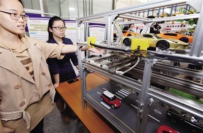 同学们展示老旧小区立体车库工作原理 本报记者 马昭 摄