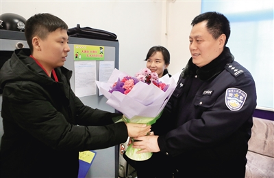 正月初一,15岁的张尚祺来到西安市公安局碑林分局红缨路派出所,将一束康乃馨送给坚守岗位的民警并向他们拜年。 本报记者 党运 摄