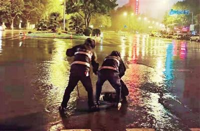 暴雨夜袭西安,城管队员冒雨排查积水点。 本报记者 马昭 摄