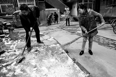 社区工作人员清扫院落 本报记者 李宗华 摄
