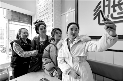 """韩女士的""""唐代仕女""""造型引众多顾客合影 本报记者 王晓峰 摄"""