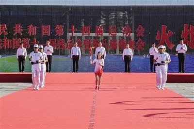 12日上午,十四运会和残特奥会火炬传递活动最后一站在西安举行。图为第1棒火炬手薛莹高擎火炬开始接力传递。 本报记者 李宗华 摄
