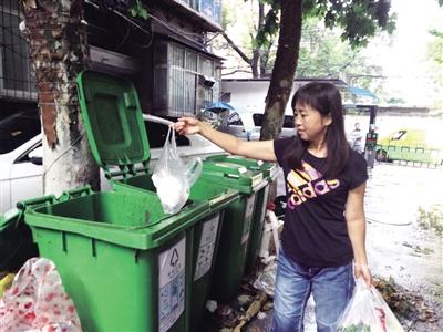 市民投放垃圾 本报记者 张毅伟 摄