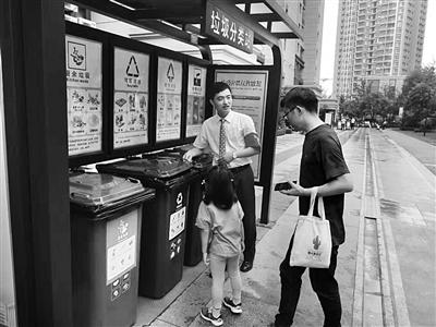 工作人员指导居民分类扔垃圾