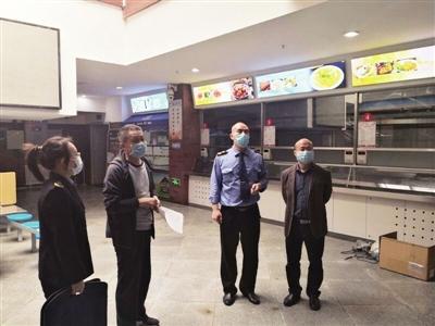执法人员检查学校食堂准备工作