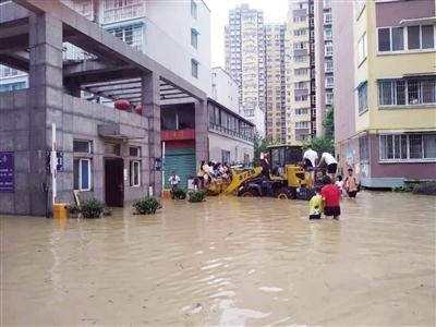 勉县一小区门前,挖掘机帮助居民转移。 (当地群众提供)