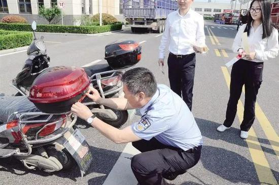 七都交警中队民警在企业为电动车粘贴反光标识。