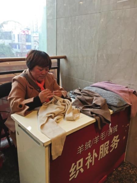 随着气温下降,织补生意也火爆起来。图为织补师正在修复一件羊绒衫。 □小圆 摄