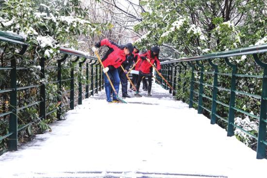 从昨天凌晨起,张家港、常熟等地下起了雪,地面出现积雪。图为市民在铲雪。 □季绍秦 摄