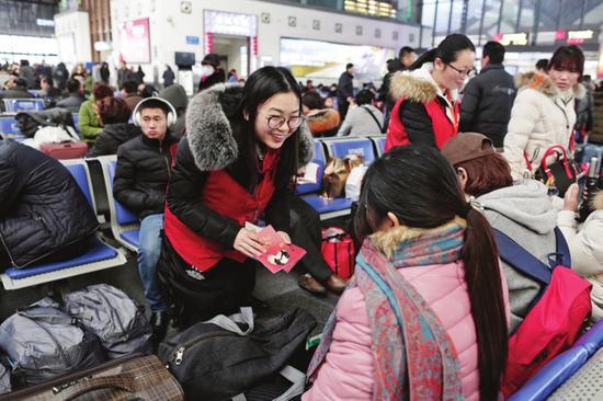 """来自苏州市未成年人健康成长指导中心的""""苏老师""""向旅客派发宣传资料。□记者 倪黎祥 摄"""