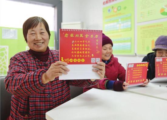 社区居民展示刚收到的《老苏州美食台历》。 □徐佳艳 摄