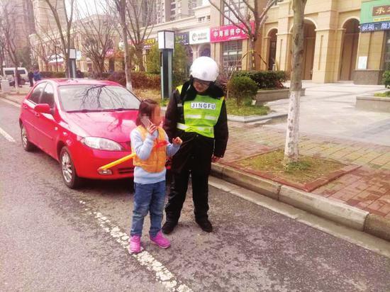 园区交警大队辅警周俊怡拉着小女孩的手帮她找妈妈。朱萍/摄