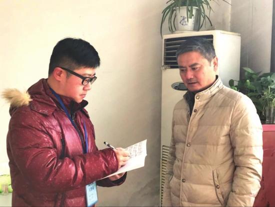 朱越(左)正在记录居民意见建议。 □陆蓉 摄