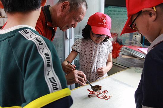 非遗传承人张爷爷在教小朋友做小猪佩奇糖画