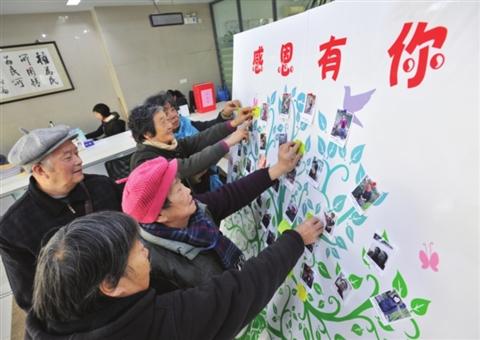 """社区工作者和居民的微笑照片和感恩心语贴了整整一面""""墙"""".图片"""