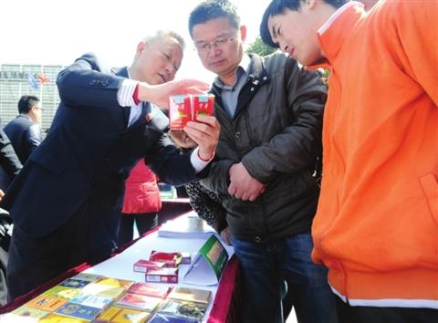 """昨天举行的""""3·15""""咨询服务活动现场,工作人员在向市民传授辨别真假香烟的方法。"""
