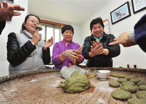金阊新城富强新苑的袁阿姨(右一)教社区新苏州人做草头饼。 □记者 徐志强 摄