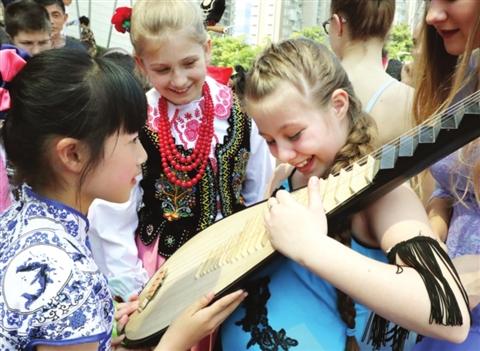 近日的国粹系列活动上,身穿青花瓷纹样旗袍的苏州小学生在教波兰小姐姐弹奏琵琶。 □记者 华雪根 摄