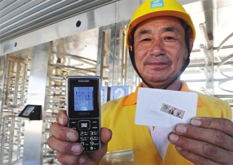 昨天,务工人员张伍贤在向记者展示手机上收到的考勤统计信息。