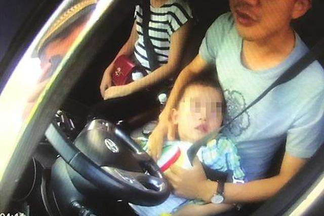 父亲抱着5岁孩子开车被罚 警方提醒:儿童不宜坐在前排