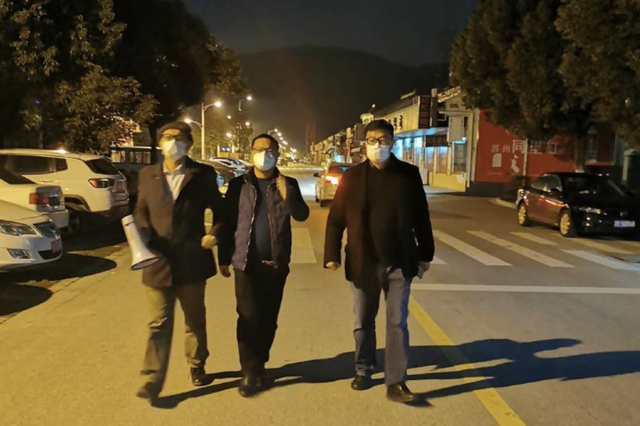 吴刚(左一)与同事正在村子内巡查防疫情况