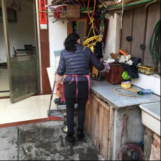 图为居家养老服务机构的服务人员到徐催男家里帮忙做家务,隔天便来一次