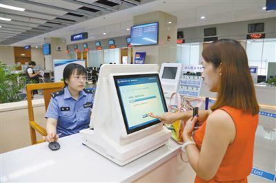 图为8月14日,工作人员正引导市民群众使用出入境智能一体机自助办理业务