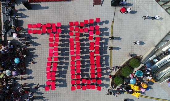 """在《我和我的祖国》的背景音乐下,现场人群手持红色展示牌,组成""""70""""字样"""