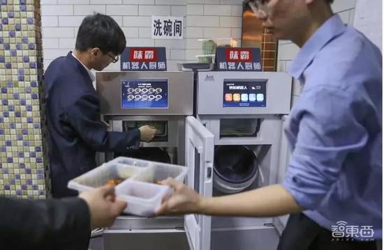 """▲工作人员在使用""""味霸""""炒菜机器人"""