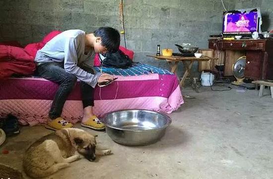 纪录片《小彪与狗》中,正在玩手机的贵州初二学生小彪。