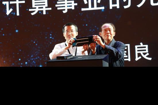 陈天石与其导师中国科技大学教授、中科院院士陈国良一起展示全新的云端智能芯片