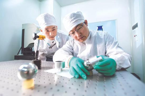 团队成员薛超及同事在研磨球体华中科技大学供图