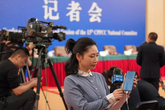 ↑3月10日,新华社记者在政协记者会开始前调试5G手机。新华社记者 何强 摄