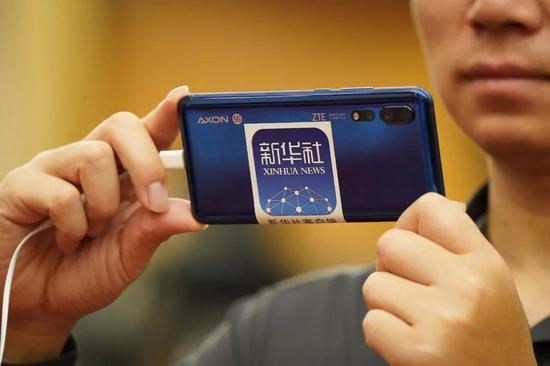 ↑3月10日,新华社记者用5G手机进行现场直播拍摄。新华社记者 何强 摄