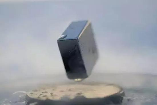 图 | 一块磁铁漂浮在超导体之上(来源:Wikimedia Commons)