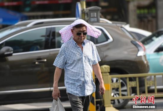 资料图:市民在高温天气出行。中新社记者 张勇 摄