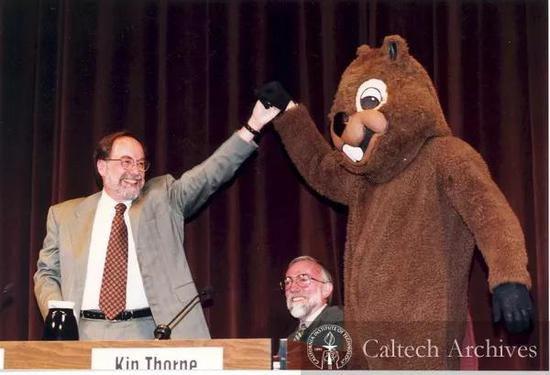 1997年,加州理工学院宣布巴尔的摩教授担任校长,巴尔的摩与加州理工学院吉祥物海狸击掌,身后为引力波项目主要发起者之一基普·索恩(Kip Thorne,2017年诺贝尔物理学奖得主) 图片来源:Caltech Archives