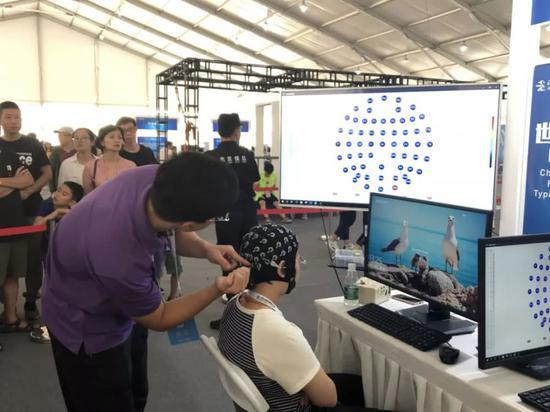 工作人员为脑电帽注射导电膏,以减少传递脑电信号的电阻。