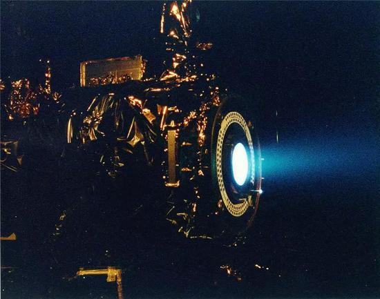 (深空一号所使用的离子电推发动机试车,发动机喷出了呈现淡蓝色的离子束。图片来源 wikipedia)